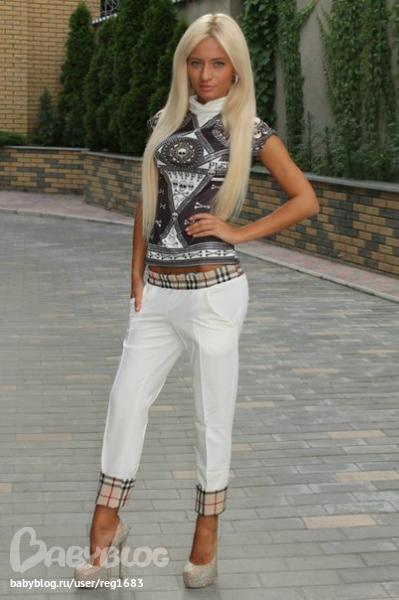 Блондинка снимает черные брюки фото